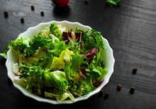 Various fresh mix salad leaves with lettuce, radicchio, and rocket in bowl. On dark wooden background Royalty Free Stock Image