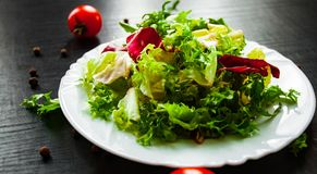 Various fresh mix salad leaves with lettuce, radicchio, and rocket in plate. On dark wooden background Stock Images