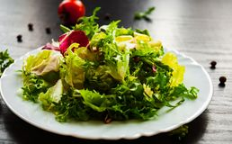 Various fresh mix salad leaves with lettuce, radicchio, and rocket in plate. On dark wooden background Stock Photo