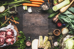 Various Fresh organic ingredients for Broth or soup cooking with vegetables and meat on dark wooden background, top view Royalty Free Stock Photography