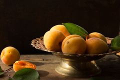 Various Fresh ripe apricots on wooden surface leaves fruits apricots on board cut apricots in half. Light blue rustic wood backgro. Fresh ripe apricots on wooden Royalty Free Stock Image