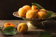 Various Fresh ripe apricots on wooden surface leaves fruits apricots on board cut apricots in half. Light blue rustic wood backgro. Fresh ripe apricots on wooden Stock Image