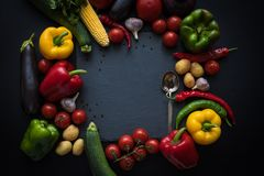 Various fresh ripe vegetables and spoon on slate board. Top view of various fresh ripe vegetables and spoon on slate board Royalty Free Stock Image