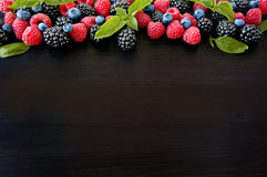 Various fresh summer berries. Ripe blueberries, raspberries and blackberries. Berries on black background. Top view with copy space Stock Images