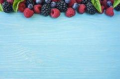 Various fresh summer berries. Ripe blueberries, raspberries and blackberries. Berries on blue background. Top view with copy space Stock Photo