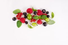 Various fresh summer berries. Ripe raspberries, currants, gooseberries, mint and basil leaves. Berries on white background. Stock Images