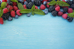 Various fresh summer berries on wooden background. Ripe blueberry, raspberry and blackberry with basil leaves. Berries at border of image with copy space for Royalty Free Stock Photos