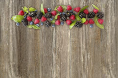 Various fresh summer berries on wooden background Royalty Free Stock Images
