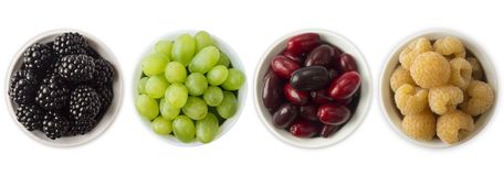Various fresh summer. Blackberries, grapes, redberries and yellow raspberries in a white bowl. Berries with copy space for text. Ripe and tasty berry isolated Stock Images