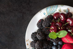 Various fresh summer fruits and berries on black stone slate background. Copy space. Top view Royalty Free Stock Photos