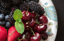 Various fresh summer fruits and berries on black stone slate background. Top view Royalty Free Stock Photography