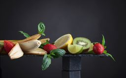 Various fresh summer fruits on black background. royalty free stock photography