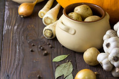 Various fresh vegetables and ceramic pot on wooden table. Cooking, healthy or vegetarian eating concept. Stock Photos