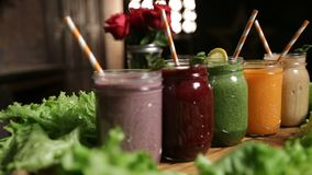 Various freshly blended smoothies on wooden tray stock video