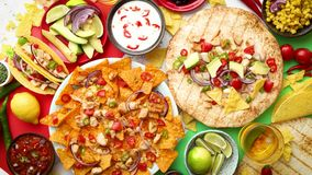 Various freshly made Mexican foods assortment. Placed on colorful table. With nachos, tacos, tortillas, grilled meat, dips, salsa and vegetables stock video