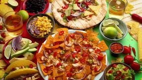 Various freshly made Mexican foods assortment. Placed on colorful table. With nachos, tacos, tortillas, grilled meat, dips, salsa and vegetables stock footage