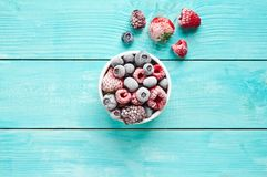 Bowl of frozen berries. Frozen berries. Various frozen berries in a bowl against blue background Stock Image