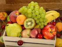Various fruit in a wooden box Stock Images