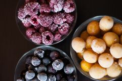 Various fruits from the freezer. Frozen raspberries, currants and cherry plums stock photos