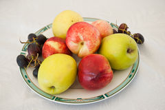 Various fruits on plate. Fresh and colored apples, grapes and nectarines on table Stock Photo