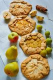 Various fruits tarts with fresh apples, plums and pears on gray concrete background. Vegetarian healthy galette - autumn dessert royalty free stock image