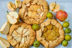 Various fruits tarts - galette with fresh apples, plums and pears on the gray concrete table. Vegetarian healthy autumn dessert stock images