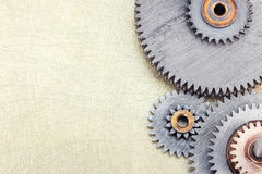 Various gear cogwheels on scratched brass background Royalty Free Stock Image