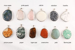 Various gemstone pendants. Collection of colorful different gemstone pendants with sterling silver Royalty Free Stock Photo
