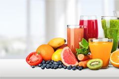 Various glasses of juice and fruits royalty free stock photos