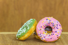 Various glazed donuts isolate on wooden background Stock Image