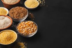 Various gluten free groats on black background with copy space. Assortment of gluten free grains in bowls on black background, copy space Stock Photo
