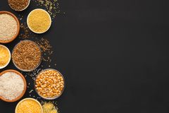 Various gluten free groats on black background with copy space. Border of assorted gluten free grains in bowls on black background, copy space, top view stock image