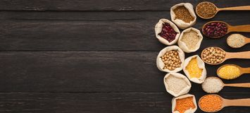 Various gluten free groats on wooden background, copy space. Border of assorted gluten free grains in cloth bags and spoons on rustic wooden background, copy stock image