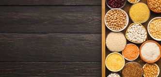 Various gluter free groats on wooden background, copy space. Border of assorted gluten free grains in bowls on rustic wooden background, copy space, top view Royalty Free Stock Image