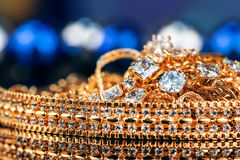 Various gold jewellery on black background Royalty Free Stock Images