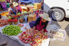Various goods in Burmese market, Myanmar. Burmese seller arranging apples in Burmese market, Myanmar. In Myanmar, eggshells are used for plants to protect plants Stock Photo