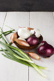 Various grades of onions: white, yellow, red onions, shallot, gr. Een onions on a white wooden table Royalty Free Stock Images