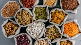 Various grains and dried fruit in hessian bags on market stall. Top view. Set of organic healthy products. Healthy eating concept royalty free stock image