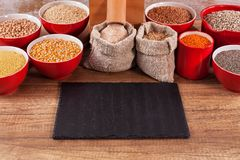 Various grains and seeds around a tabletop mill royalty free stock image