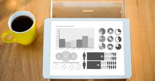 Various graphs on digital tablet by coffee cup at table Royalty Free Stock Image