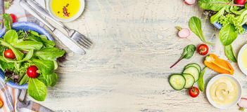 Various green organic salad ingredients on  light rustic background, top view, banner. Royalty Free Stock Images