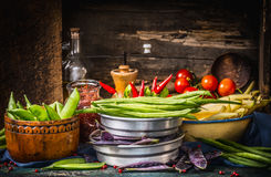 Various green and white beans pods in bowls with cooking ingredients on dark rustic kitchen table Stock Image