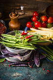 Various green and white beans pods in bowls with cooking ingredients on dark rustic kitchen table Royalty Free Stock Image