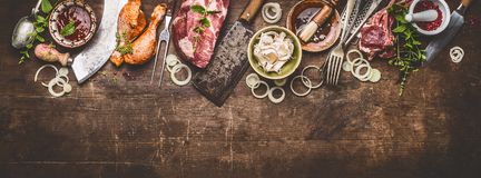 Various grill an bbq meats on rustic wooden background with aged kitchen and butcher tools. Herbs, spices, seasoning and sauce, top view, border royalty free stock image
