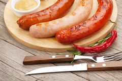 Various grilled sausages with condiments Stock Photos