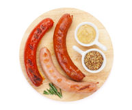 Various grilled sausages with condiments Stock Photography