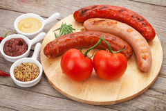 Various grilled sausages with condiments and tomatoes Royalty Free Stock Image