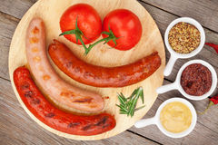 Various grilled sausages with condiments and tomatoes Stock Photos