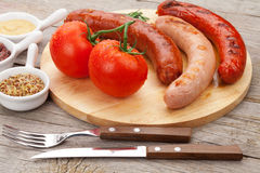 Various grilled sausages with condiments and tomatoes Royalty Free Stock Photos