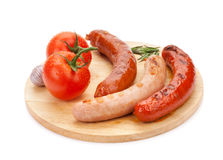 Various grilled sausages and tomatoes Royalty Free Stock Images